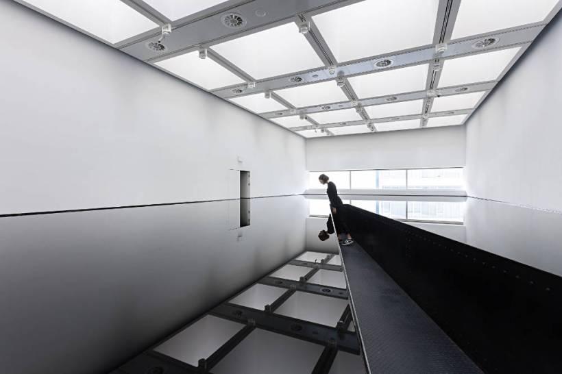 אישה עומדת בתערוכת משני צורה בגלריית הייווארד מתבוננת על משטח