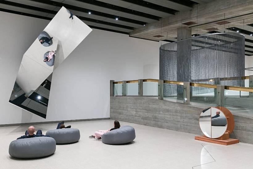 מבקרים יושבים במיצג אומנות בשם משני צורה במוזיאון הייווארד