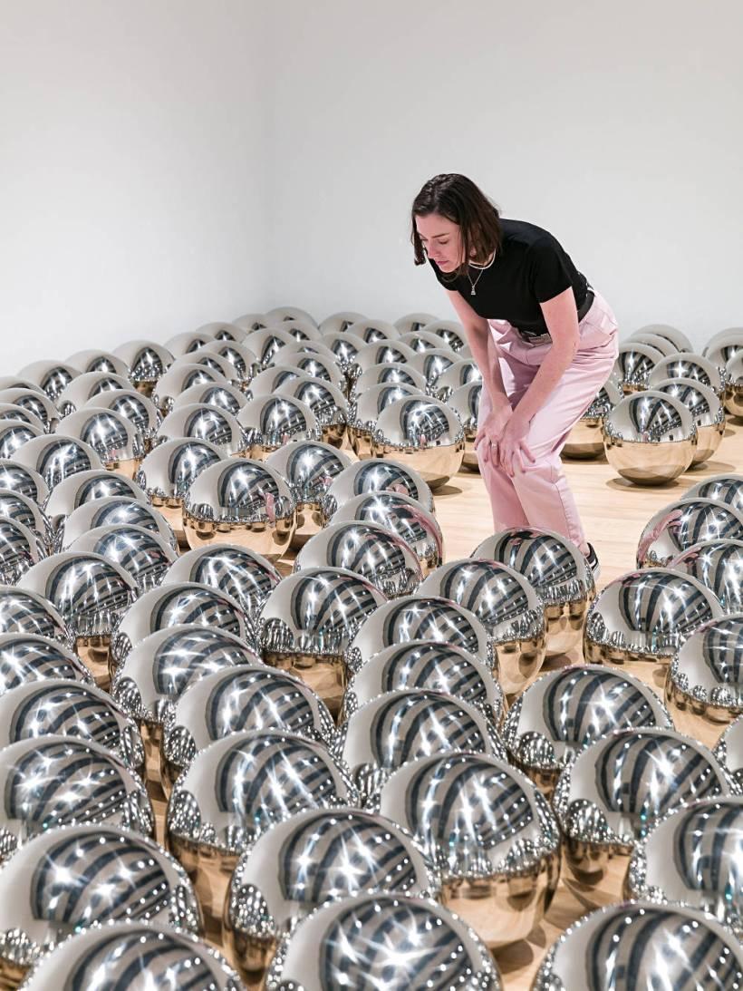 אישה מתבוננת בכדורי מתכת חלק מתערוכה בשם משני צורה בגלריית הייווארד